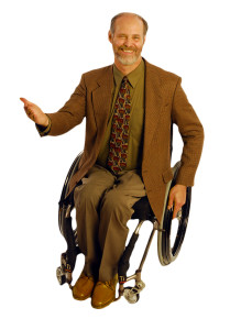 Gary Karp in a wheelchair wearing a jacket and tie gesturing with his right hand.